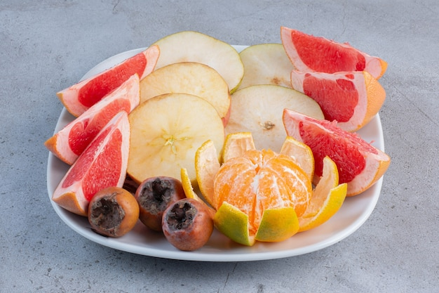 Een schotel van gesneden grapefruits, peren en een gepelde mandarijn op marmeren achtergrond.