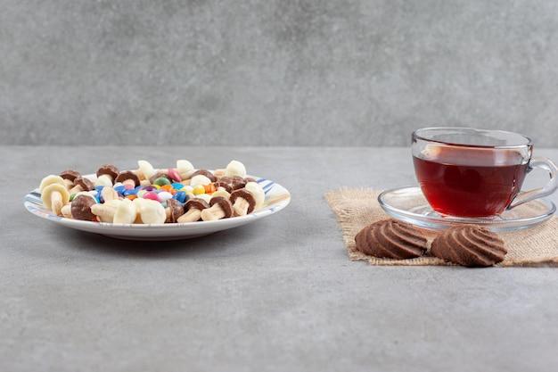 Een schotel van snoepjes en chocoladepaddestoelen naast een kopje thee en koekjes op marmeren achtergrond. hoge kwaliteit foto