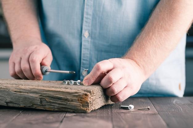 Een schroef in hout schroeven met een schroevendraaier