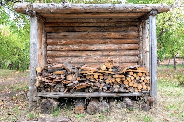 Een schuur met een schuur voor brandhout staat in de tuin van een dorpshuis landelijke levensstijl