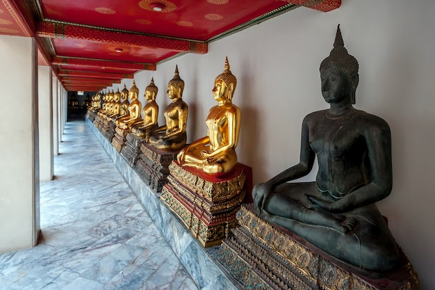 Een sculptuur van donkere en vele gouden boeddha's zit in lotushouding in een rij op een marmeren vloer