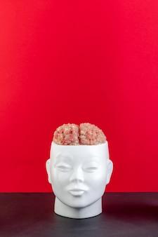 Een sculptuur van een wit mensenhoofd gevuld met gehakt tegen een rode en zwarte achtergrond. conceptuele fotografie. sjabloon voor ontwerp.