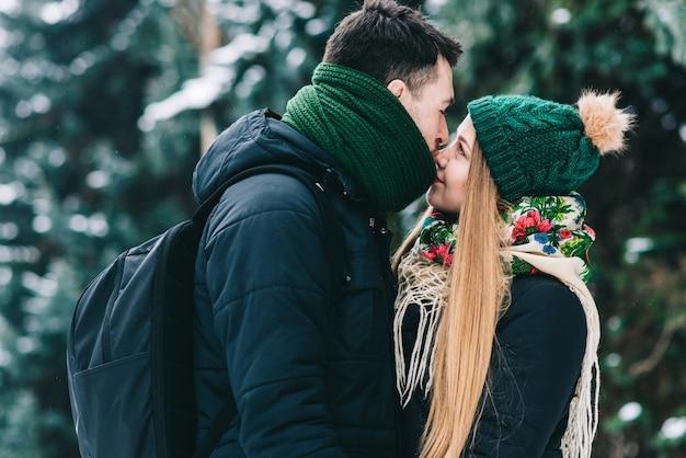 Een seconde voor de kus. speels liefdevol stel heeft plezier in het winterpark. ze knuffelen en lachen. man bereidt zich voor om zijn vriendin te kussen