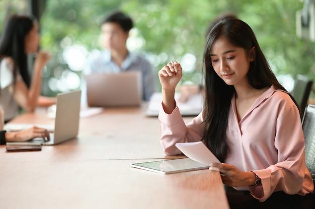 Een secretaressevrouw schrijft op een computertablet terwijl ze in de vergaderruimte zit.