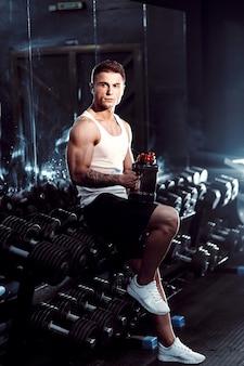 Een seksueel getrainde man drinkt sportvoeding na een sterke training, handen, voeten, rug, biceps en triceps