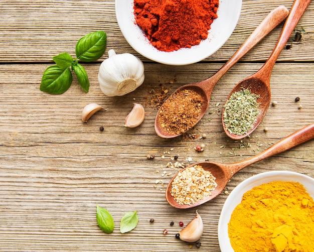 Een selectie van verschillende kleurrijke kruiden op een houten tafel in kommen en lepels
