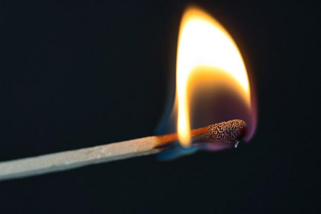 Een selectieve focus van een lucifer in brand op zwarte achtergrond