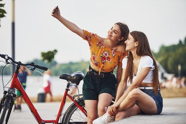 Een selfie maken. twee jonge vrouwen met fiets hebben een goede tijd in het park.