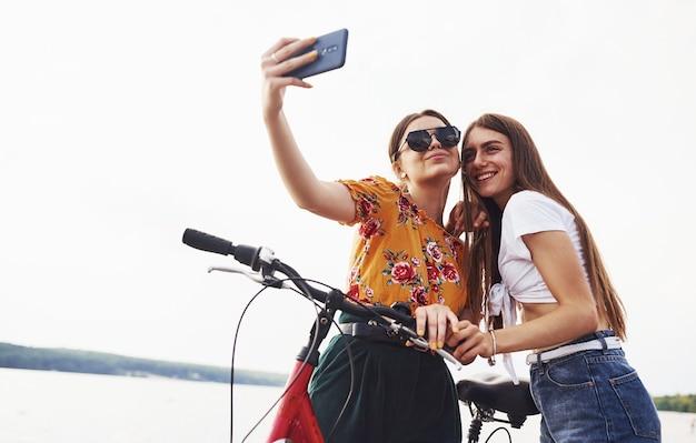 Een selfie maken. twee vriendinnen op de fiets hebben plezier op het strand bij het meer.