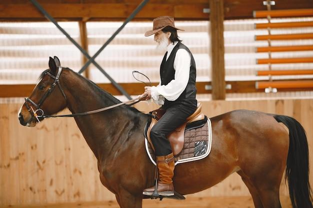 Een senior man die dicht bij een paard buiten in de natuur staat