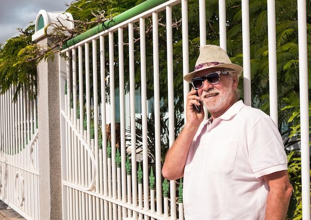 Een senior man die tegen een witte poort in de tuin staat te praten met zijn mobiele telefoon. zonnebril voor de zonnige dag.