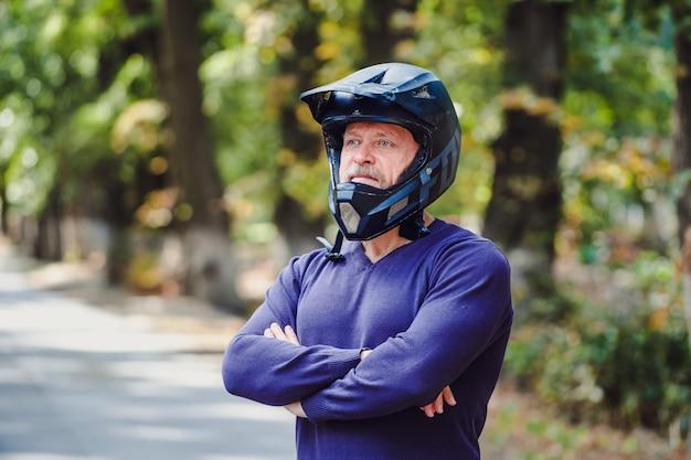 Een senior man in donkere helm buiten. casual kleding. gekruiste handen. blauwe trui. outdoor onscherpe achtergrond. detailopname.