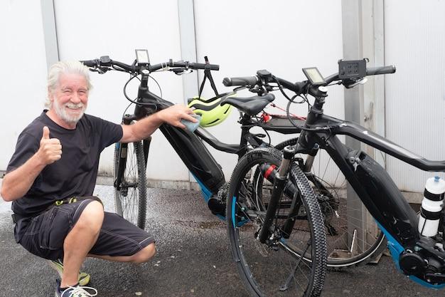Een, senior man is klaar met het wassen van de twee fietsen en steekt zijn duim op als teken van overwinning.
