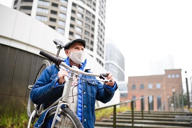 Een senior man met fiets buiten op straat in de stad, coronavirus concept.