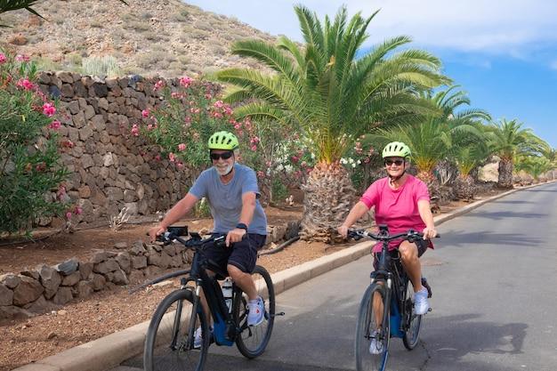 Een senior paar man en vrouw genieten van vrijheid met elektrische fiets. geluk, plezier en emotie buiten op straat. bloeiende planten en palmbomen op de achtergrond