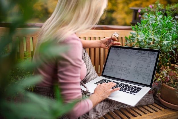 Een senior vrouw architect met laptop zittend buiten op terras, werken.