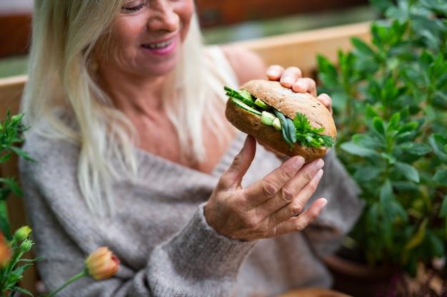 Een senior vrouw buiten op terras, groentesandwich etend.