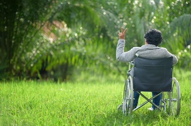 Een senior vrouw in een rolstoel heeft een sterke aanwezigheid in de tuin gelukkig oude vrouw op een rolstoel