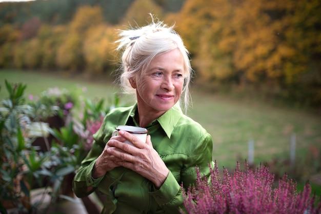 Een senior vrouw met koffie die buiten op het terras staat, rustend.