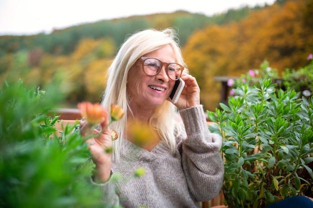 Een senior vrouw zit buiten op het terras, met behulp van smartphone.