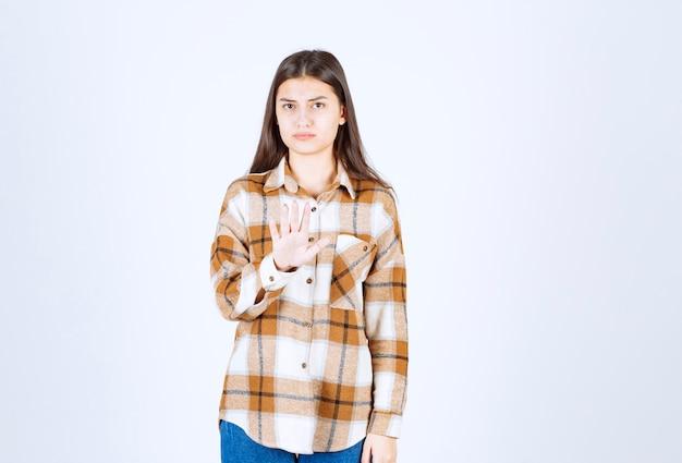 Een serieus jong meisjesmodel dat staat en een stopbord toont.