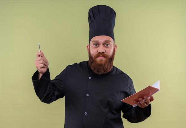 Een serieuze, bebaarde chef-kok in zwart uniform houdt notitieboekje en potlood vast terwijl hij kijkt en probeert iets uit te leggen op een groene muur