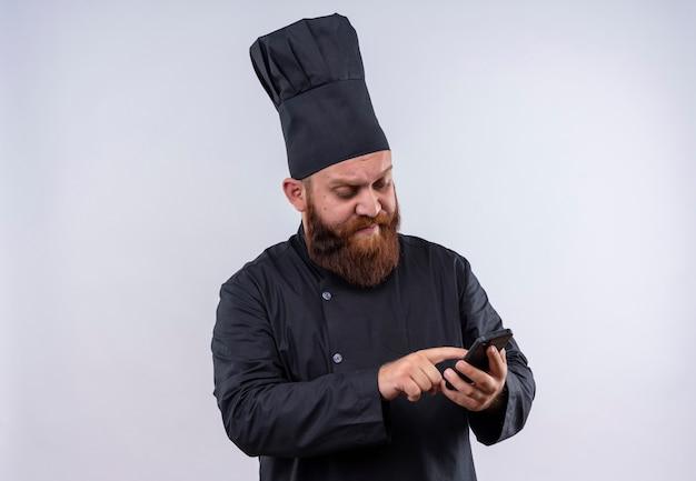 Een serieuze bebaarde chef-kok in zwart uniform raakt zijn mobiele telefoon aan op een witte muur