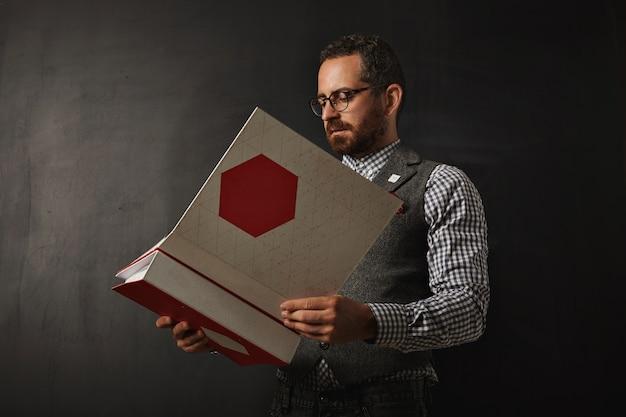 Een serieuze, bebaarde professor in een geruit oxford overhemd en tweed vest leest een nieuw onderwijsplan voor zijn student voor volgend jaar op de universiteit