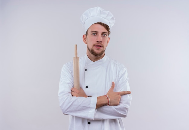 Een serieuze jonge, bebaarde chef-kokmens die een wit fornuisuniform draagt en een hoed die de deegroller vasthoudt en naar de zijkant wijst terwijl hij op een witte muur kijkt