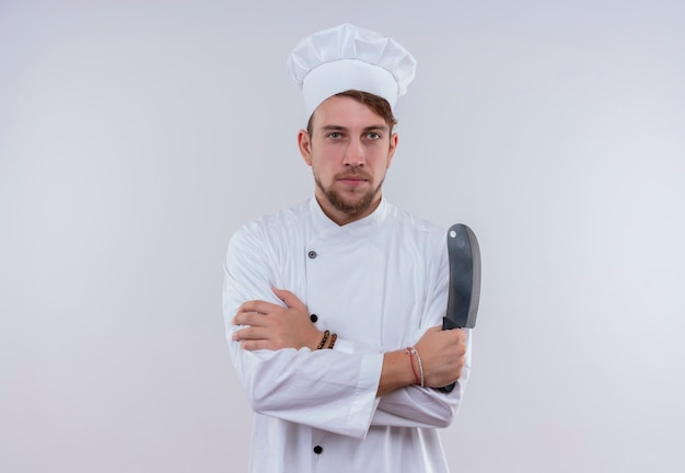 Een serieuze jonge, bebaarde chef-kokmens die een wit fornuisuniform draagt en een hoed houdt die vleesmes vasthoudt terwijl hij op een witte muur kijkt Gratis Foto