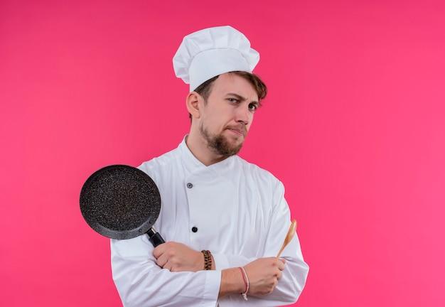 Een serieuze jonge, bebaarde chef-kokmens in wit uniform die een pan met houten lepel houdt terwijl hij op een roze muur kijkt