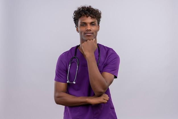 Een serieuze jonge knappe donkere arts met krullend haar, gekleed in violet uniform met een stethoscoop die de hand op de kin houdt