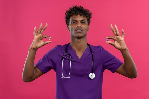 Een serieuze jonge knappe donkere arts met krullend haar, gekleed in violet uniform met een stethoscoop met pillen