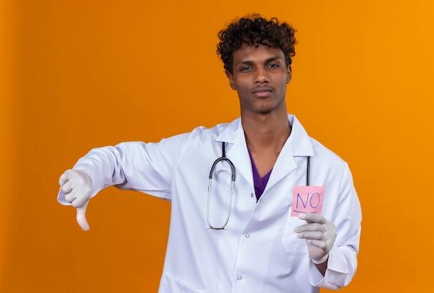 Een serieuze jonge knappe donkere man met krullend haar, gekleed in een witte jas met een stethoscoop en een papieren kaart met het woord nee