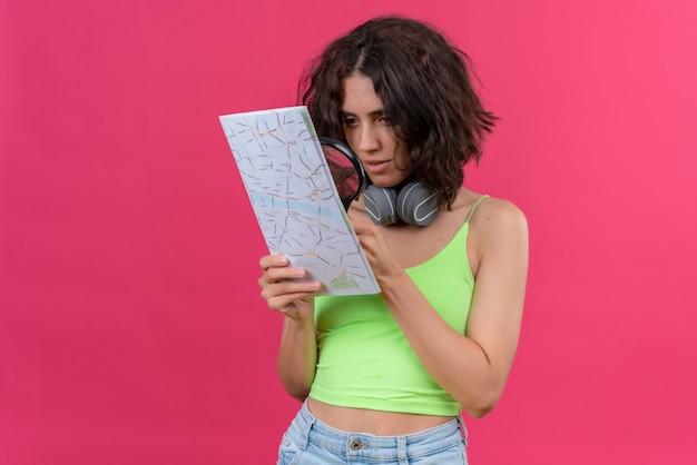 Een serieuze jonge mooie vrouw met kort haar in een groene crop top in koptelefoon kijken naar een kaart met vergrootglas