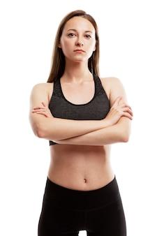 Een serieuze jonge vrouw in sportkleding staat met haar armen gekruist op haar borst