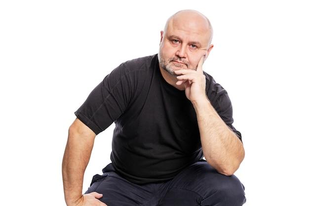 Een serieuze kale man van middelbare leeftijd in een zwart t-shirt zit met zijn hand in zijn gezicht. over wit wordt geïsoleerd.