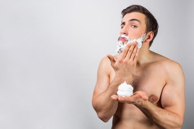 Een serieuze kerel legt wat scheerschuim op zijn baard. deze bijna dagelijkse routine houdt hem in tonus. weergave knippen. geïsoleerd op witte muur