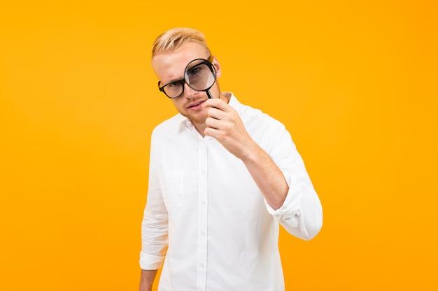 Een serieuze man met een bril is op zoek naar iets met een vergrootglas, foto geïsoleerd op geel
