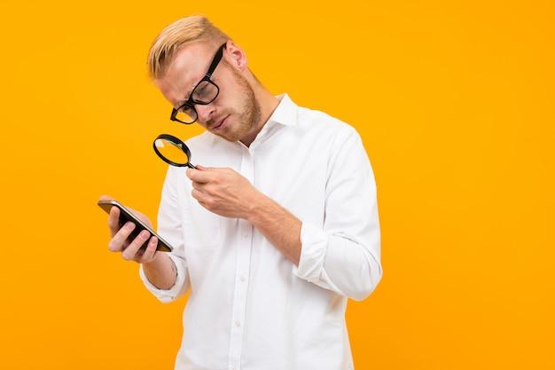 Een serieuze man met een bril is op zoek naar iets met een vergrootglas, foto geïsoleerd op gele achtergrond