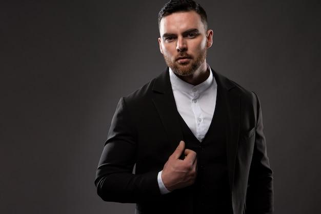 Een serieuze modezakenman met een baard, gekleed in een zwart pak en een wit overhemd