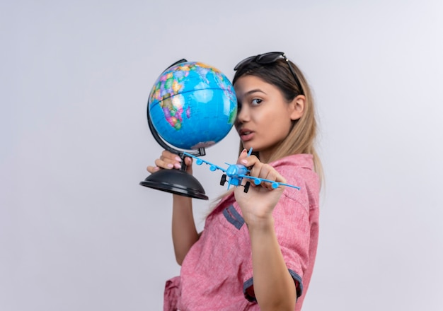 Een serieuze mooie jonge vrouw met een rood shirt in een zonnebril die een wereldbol en een blauw speelgoedvliegtuig vasthoudt terwijl ze op een witte muur kijkt