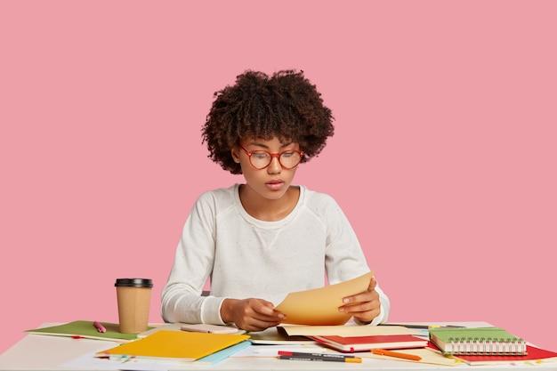 Een serieuze professionele ontwerper controleert ontwerpschetsen, zit op het bureaublad en leest de documentatie
