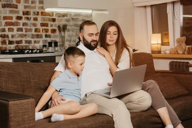 Een serieuze vader met een baard probeert op afstand te werken op een laptop in de buurt van zijn zoon en een nieuwsgierige vrouw thuis