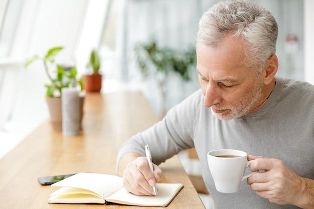 Een serieuze volwassen senior zakenman zit in café en schrijft notities in een notitieblok die koffie drinkt.