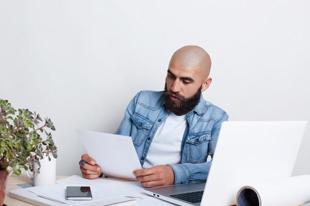 Een serieuze zakenman met baard en snor die het overhemd van jean draagt dat met documenten bezig is.