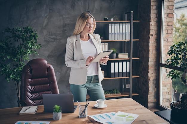 Een serieuze, zelfverzekerde, geconcentreerde ceo concentreerde zich op het controleren van rapporten van haar werknemers die aan tafel stonden met grafieken erop