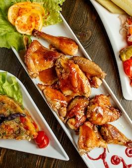 Een serveerschaal met stukjes gegrilde kip gegarneerd met saus