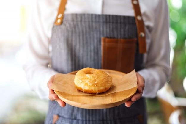 Een serveerster die een stuk van eigengemaakte doughnut in houten dienblad houdt en dient
