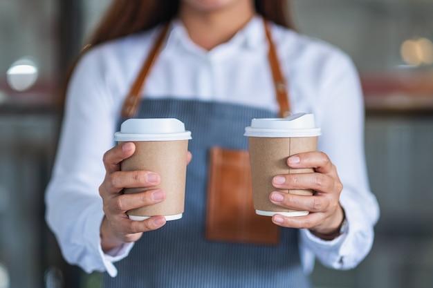 Een serveerster die twee papieren kopjes warme koffie vasthoudt en serveert in café